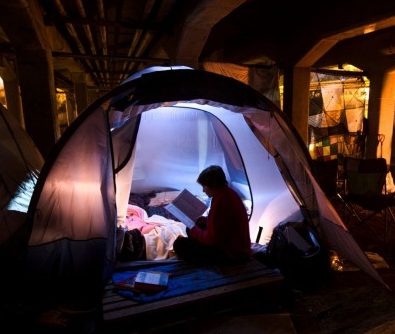 homeless reading in tent
